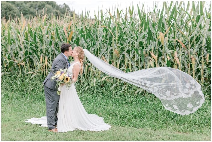couple kissing by corn field