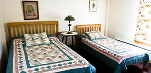 room with hand stenciled walls and quilts