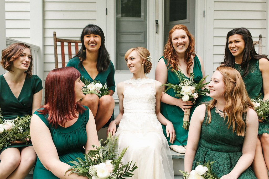 bride and bridesmaids sitting on porch